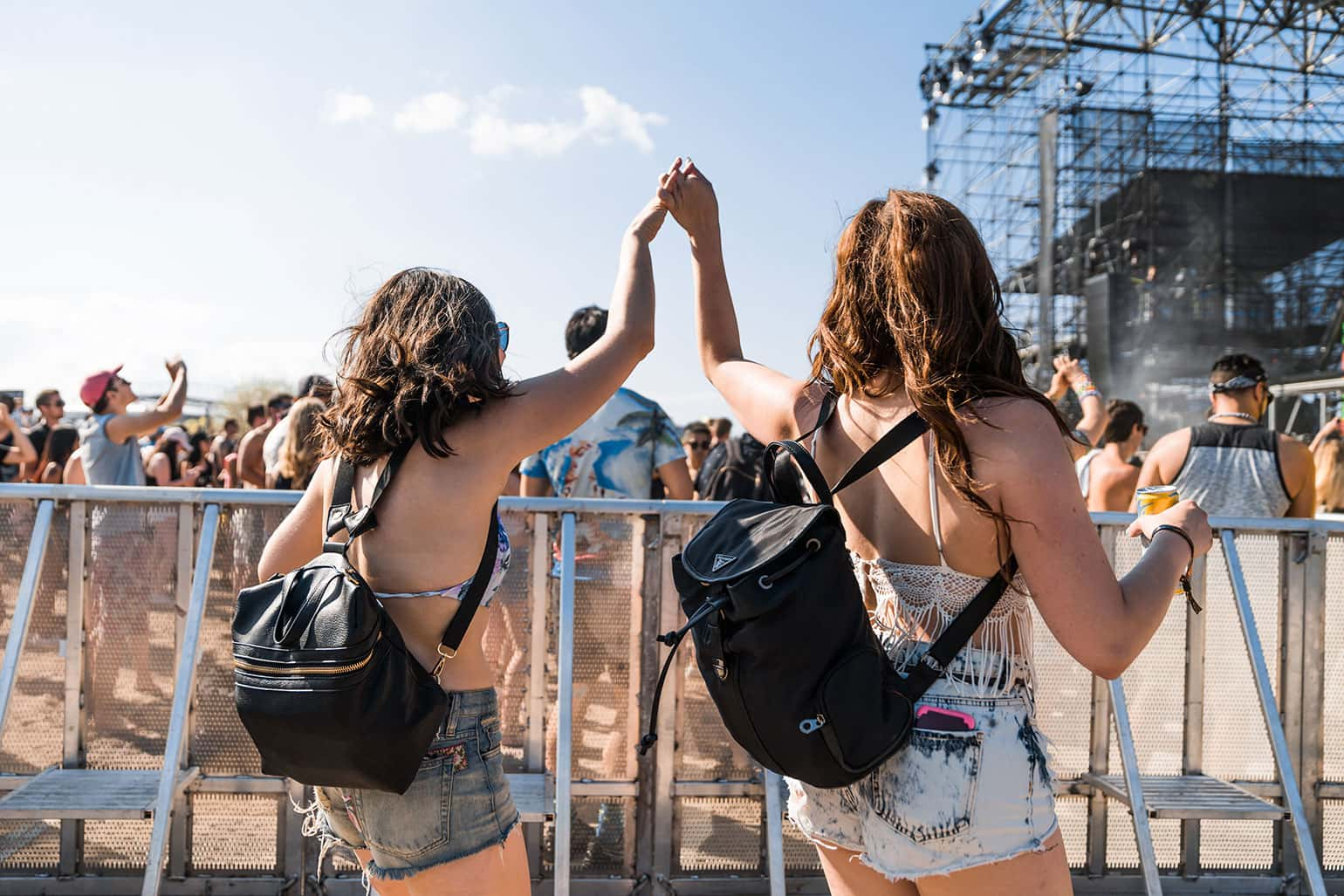 Two similarly dressed young women celebrate at an outdoor music festival.
