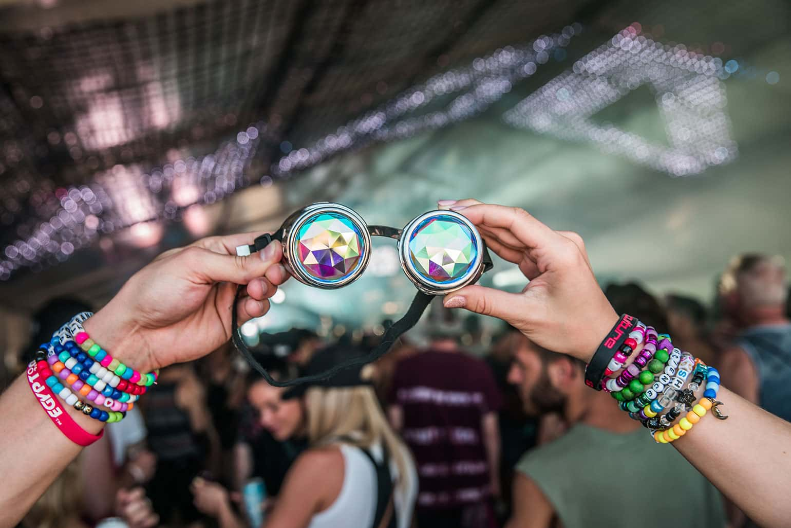 Concert-going couple with festival wristbands holding a pair of prismatic sunglasses.