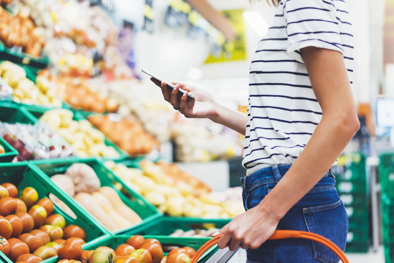Young woman using smart phone in supermarket to shop for healthy food.