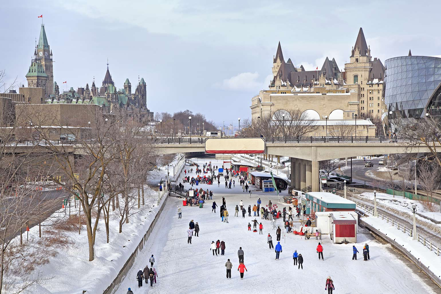 Rideau Canal skating rink during Winterlude with Parliament of Canada overlooking skaters.