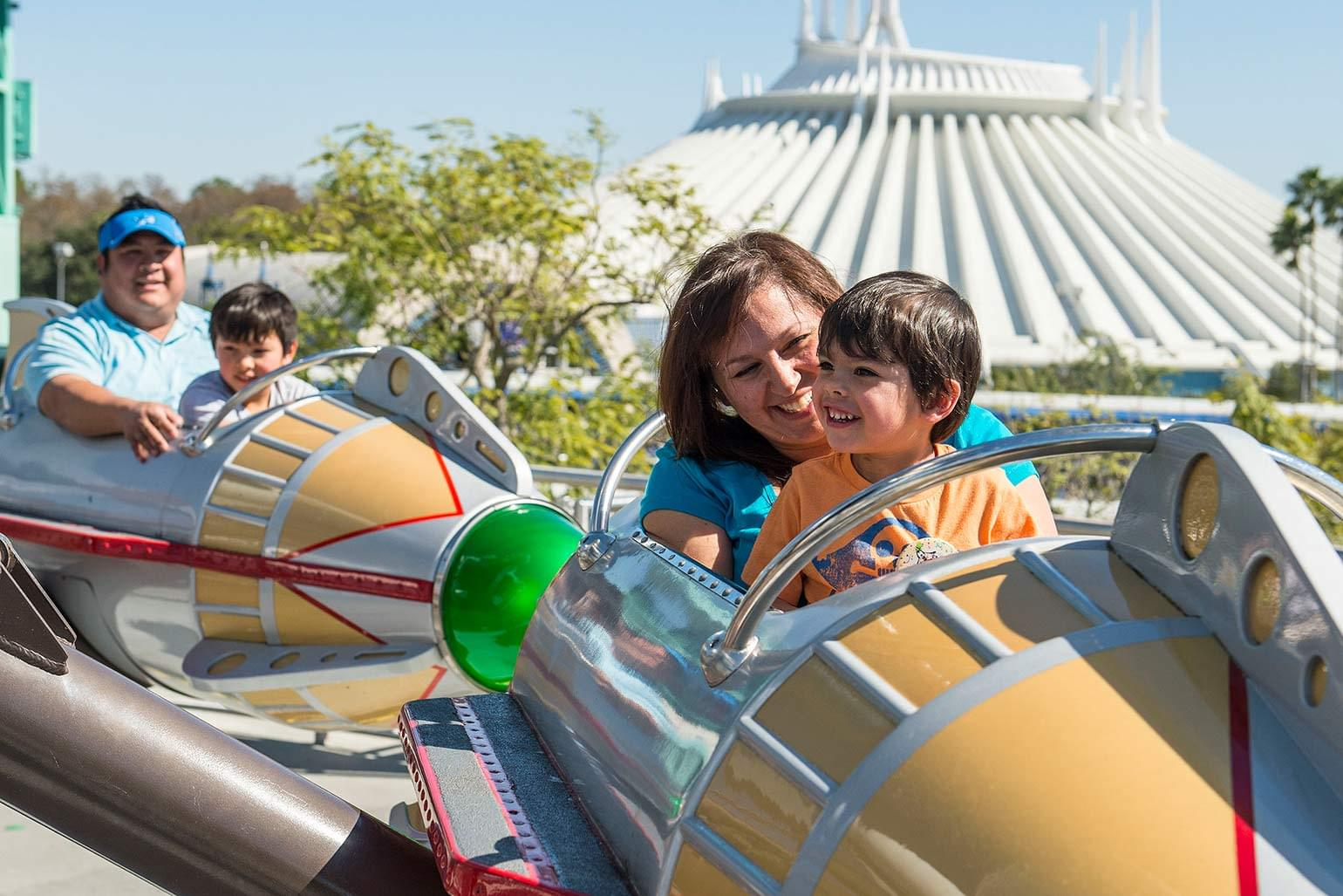 Smiling family enjoys the Astro Orbitor ride in Tomorrowland.