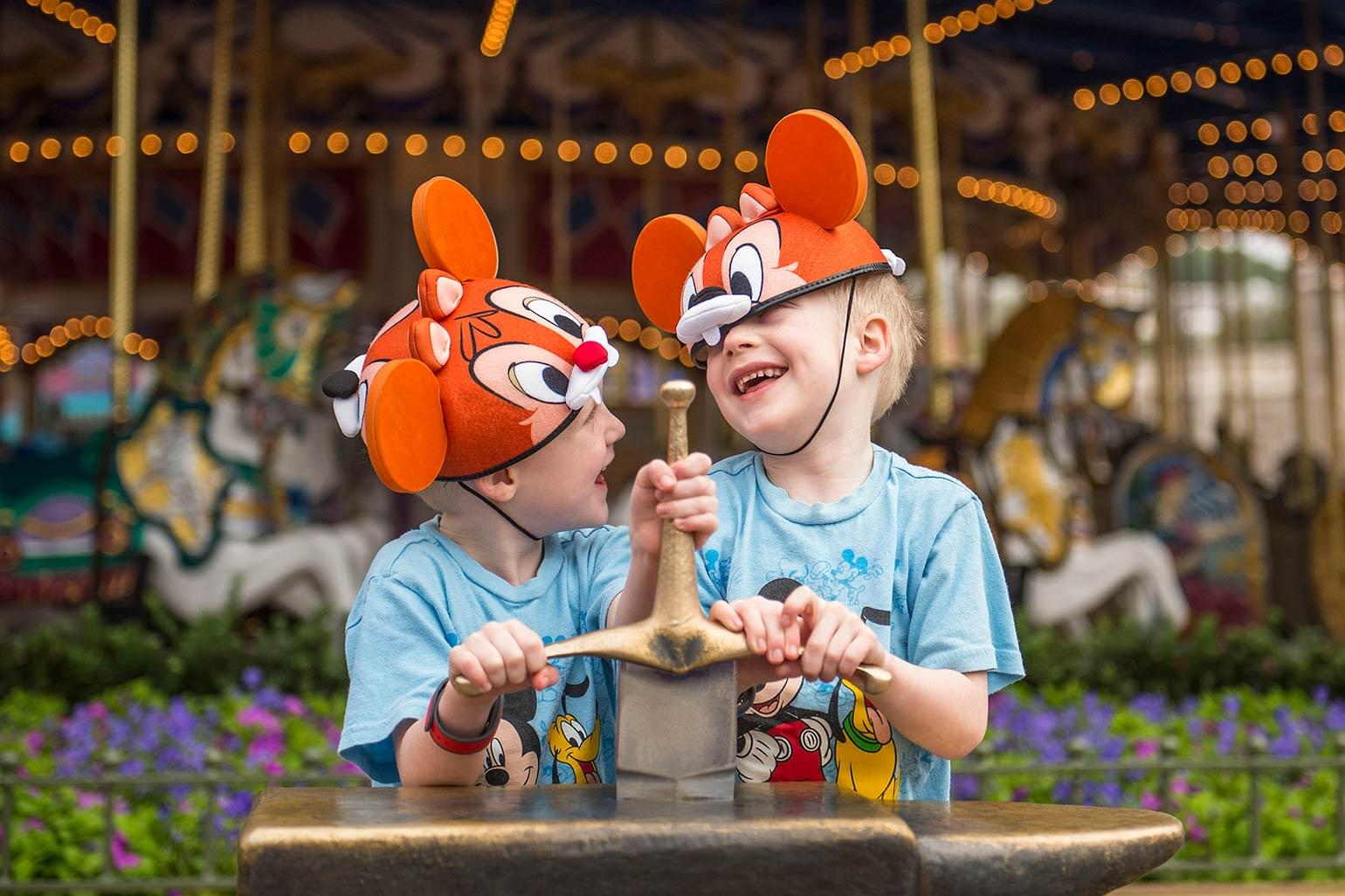 Two young brothers laugh while trying to pull out the sword in the stone at the Magic Kingdom.