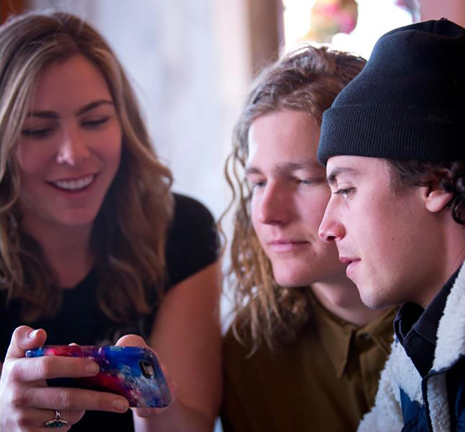 Mark McMorris stares at phone screen with Aspen locals