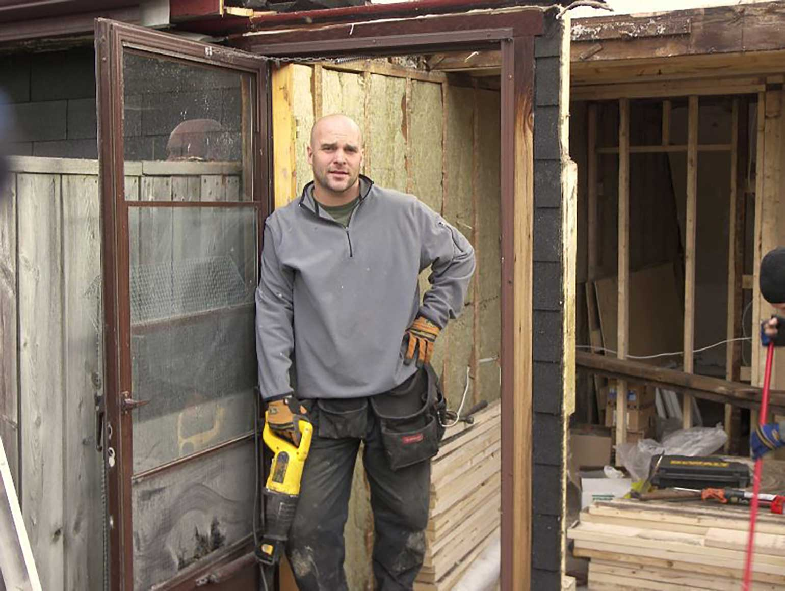 Bryan leaning in a doorway of an obviously gutted house.