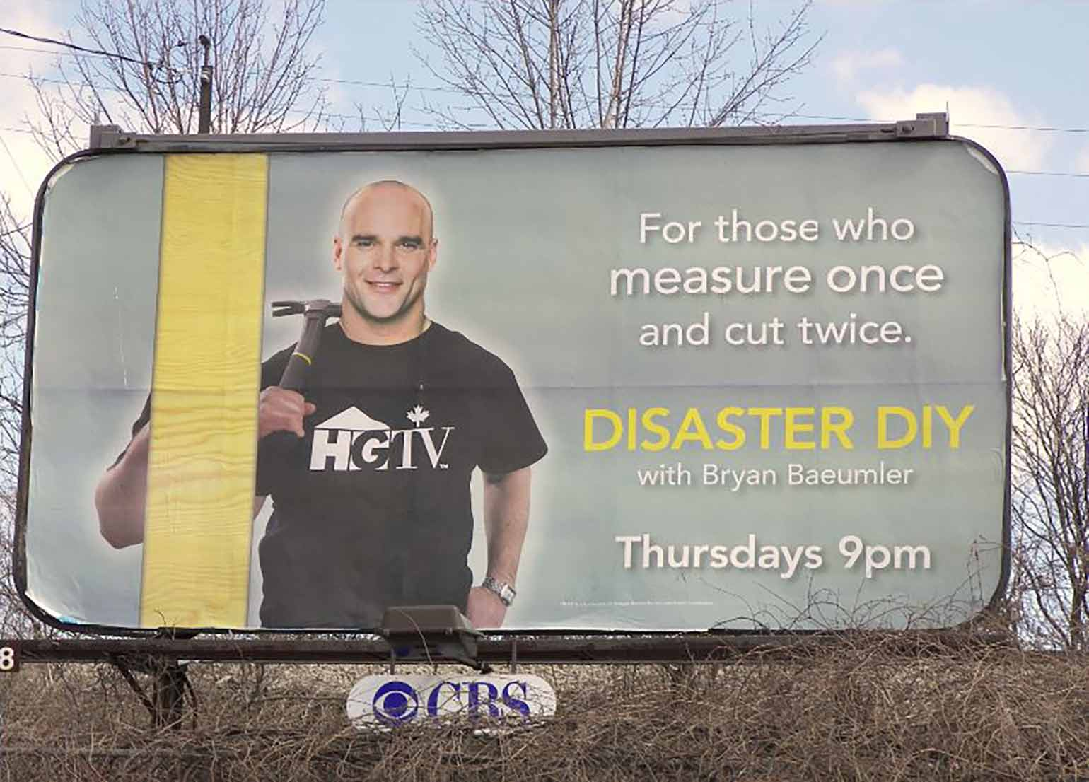 Image of a billboard with Bryan Baeumler holding a hammer. Billbaord reads: DIY Disasters. For Those Who Measure Once and Cut Twice.