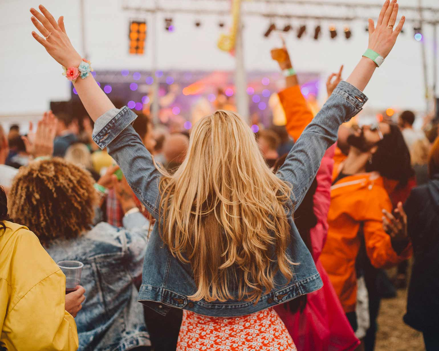 Young girl standing in a crowd at a music festival looking towards the stage.
