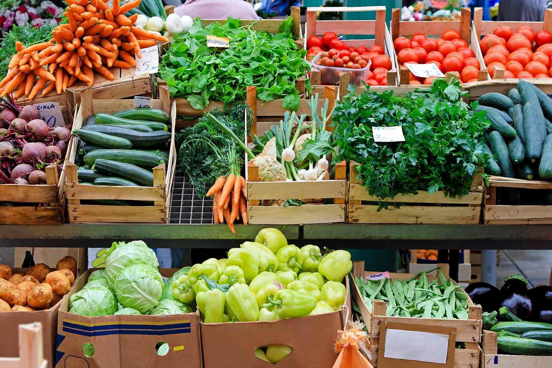 Des cageots de légumes assortis sur un étal dans un marché de producteurs.