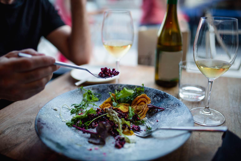 Une salade et une bouteille de vin partagées par deux personnes.