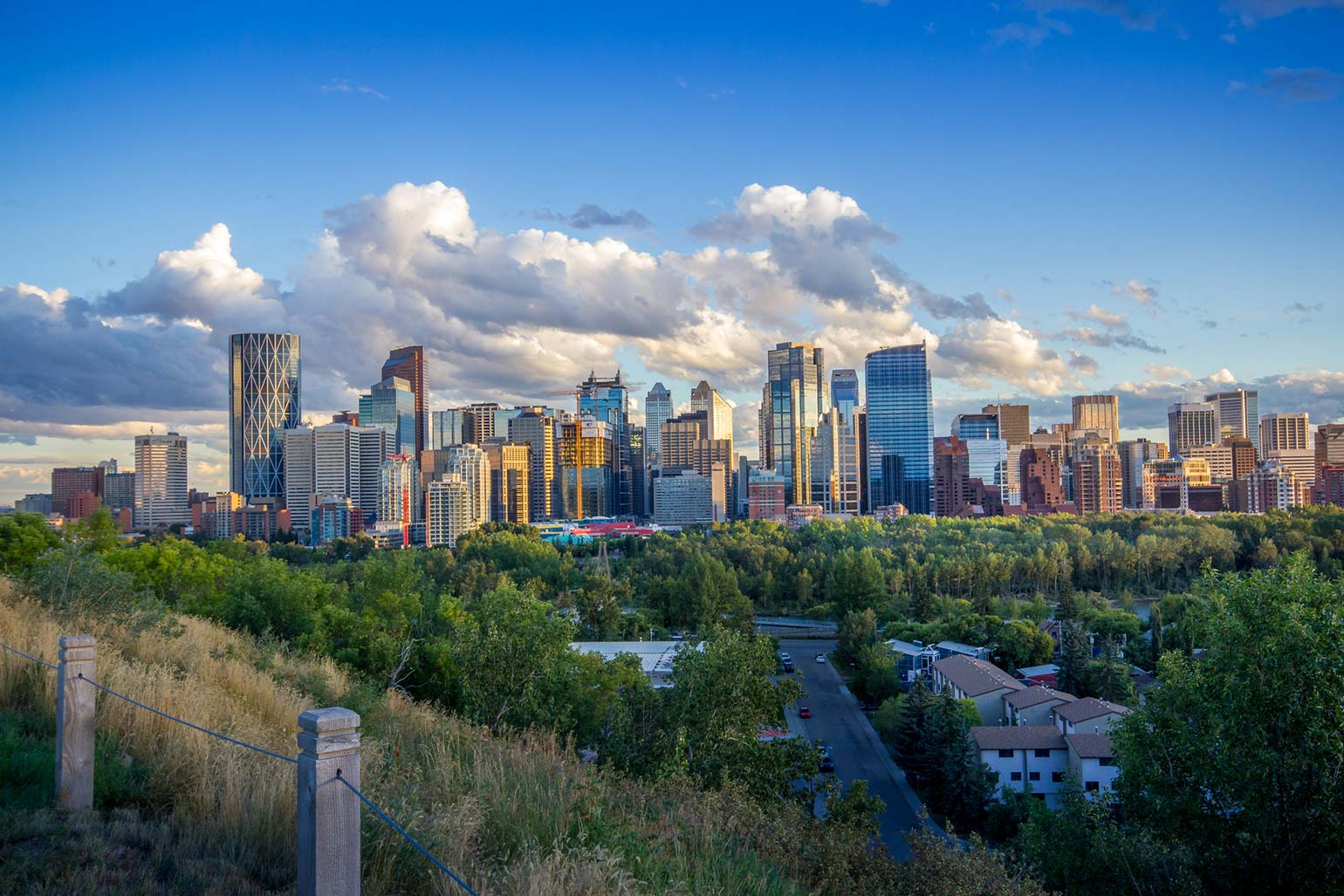 View of downtown Calgary and its buildings while clouds float in the sky above.
