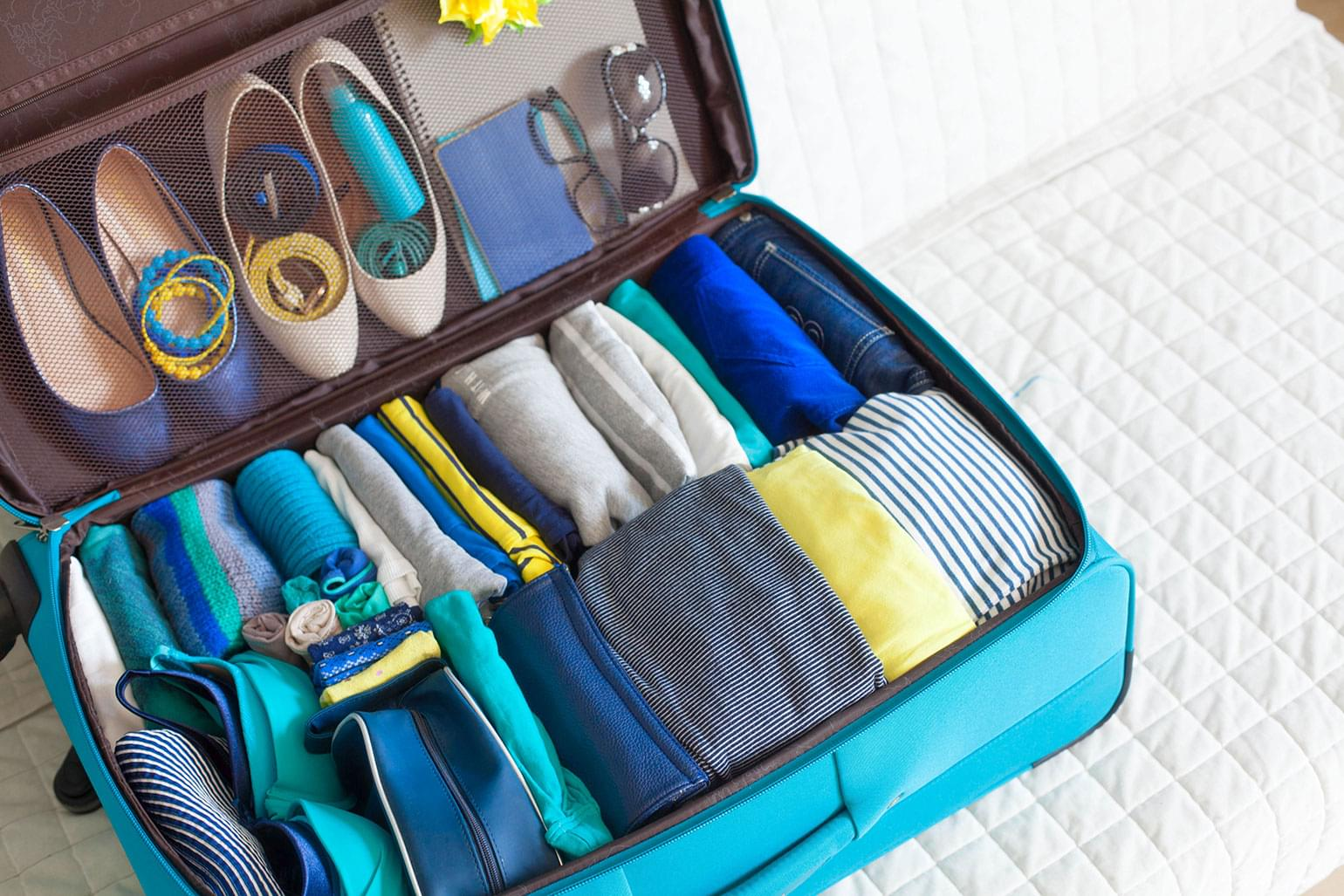 Suitcase packed neatly with clothes rolled and organized.