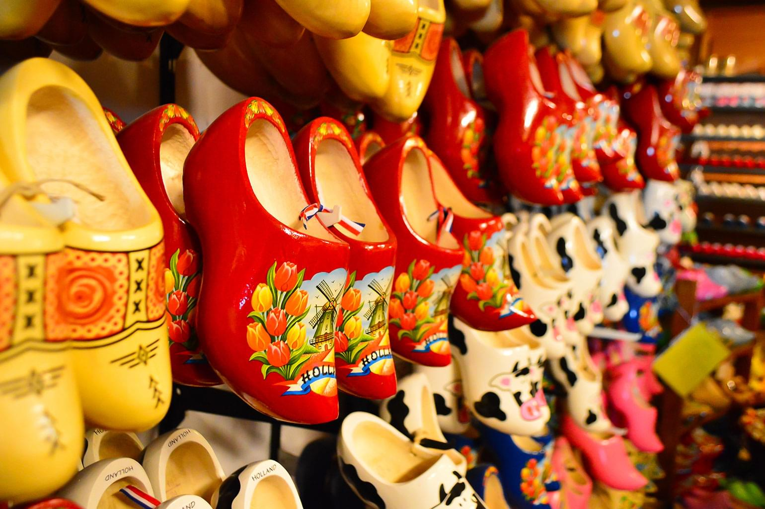 Rows of Dutch painted wooden shoes on display in a shop.