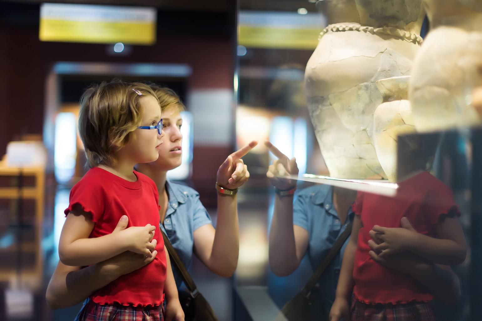 Woman and child looking at ancient Greek pottery in historical museum.