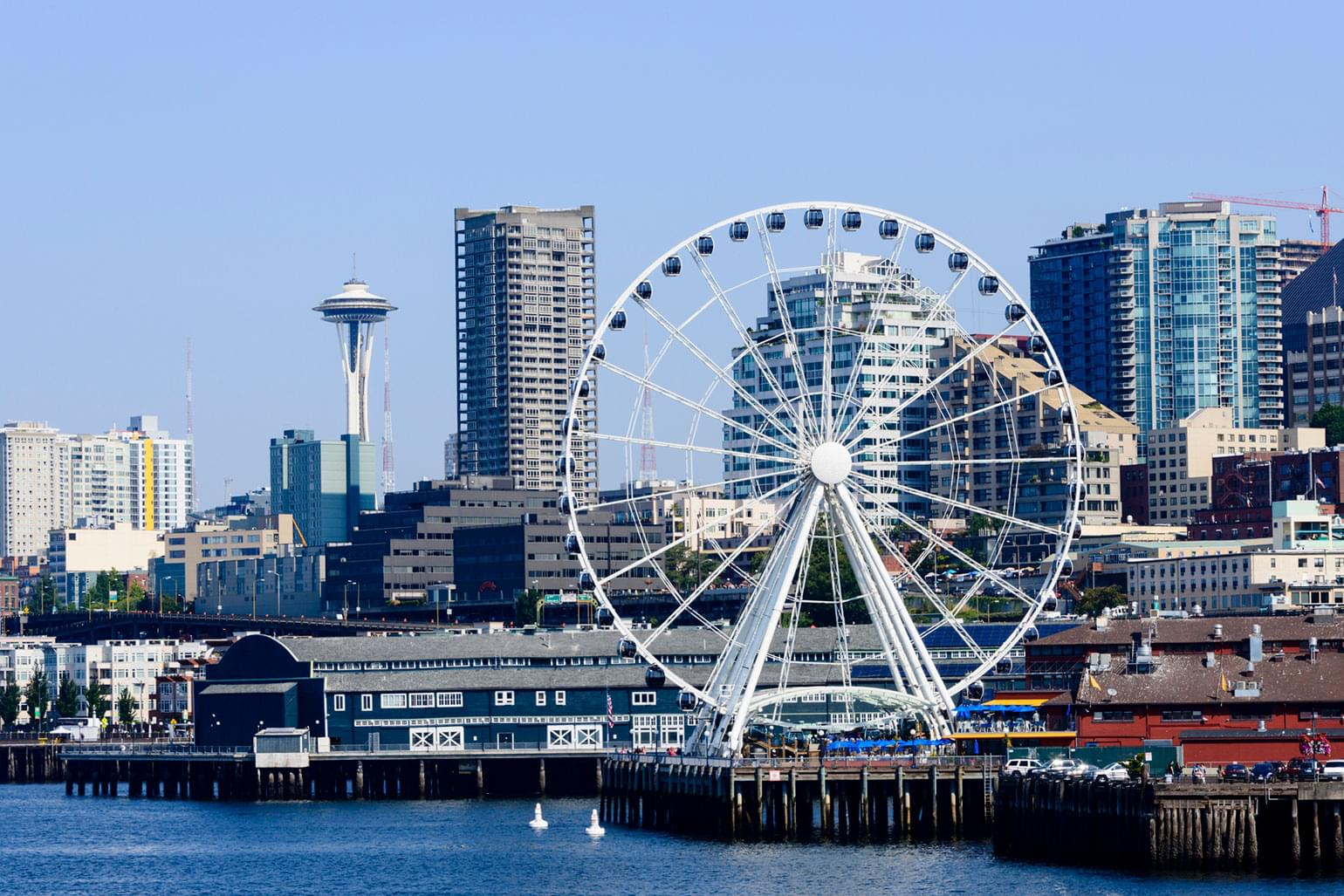 A view of downtown Seattle with the ferris wheel at the Seattle pier and the Space Needle national landmark.