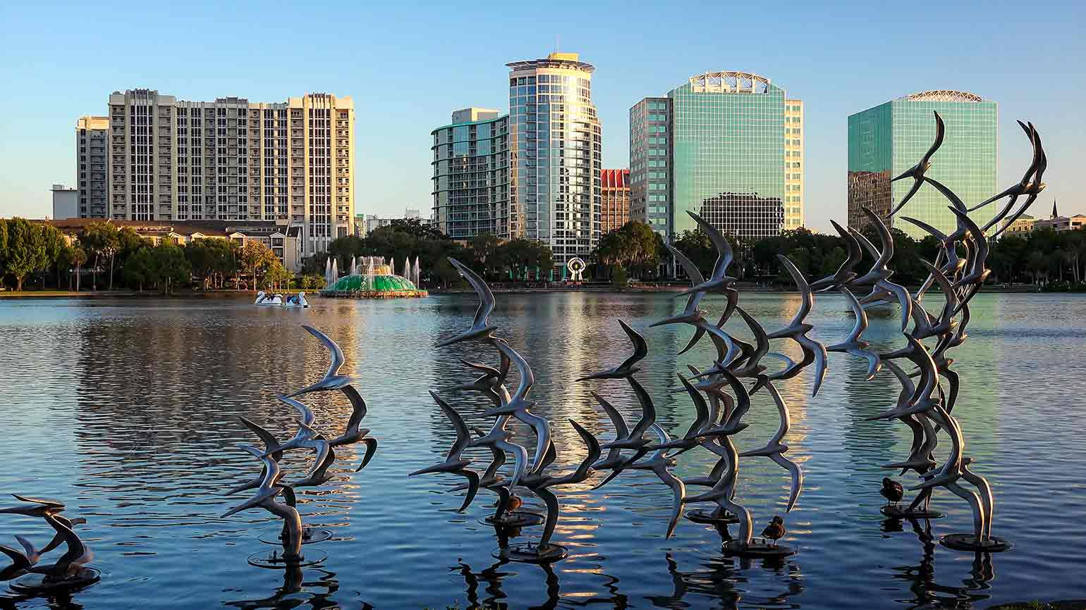 birds sculpture above water with city skyline