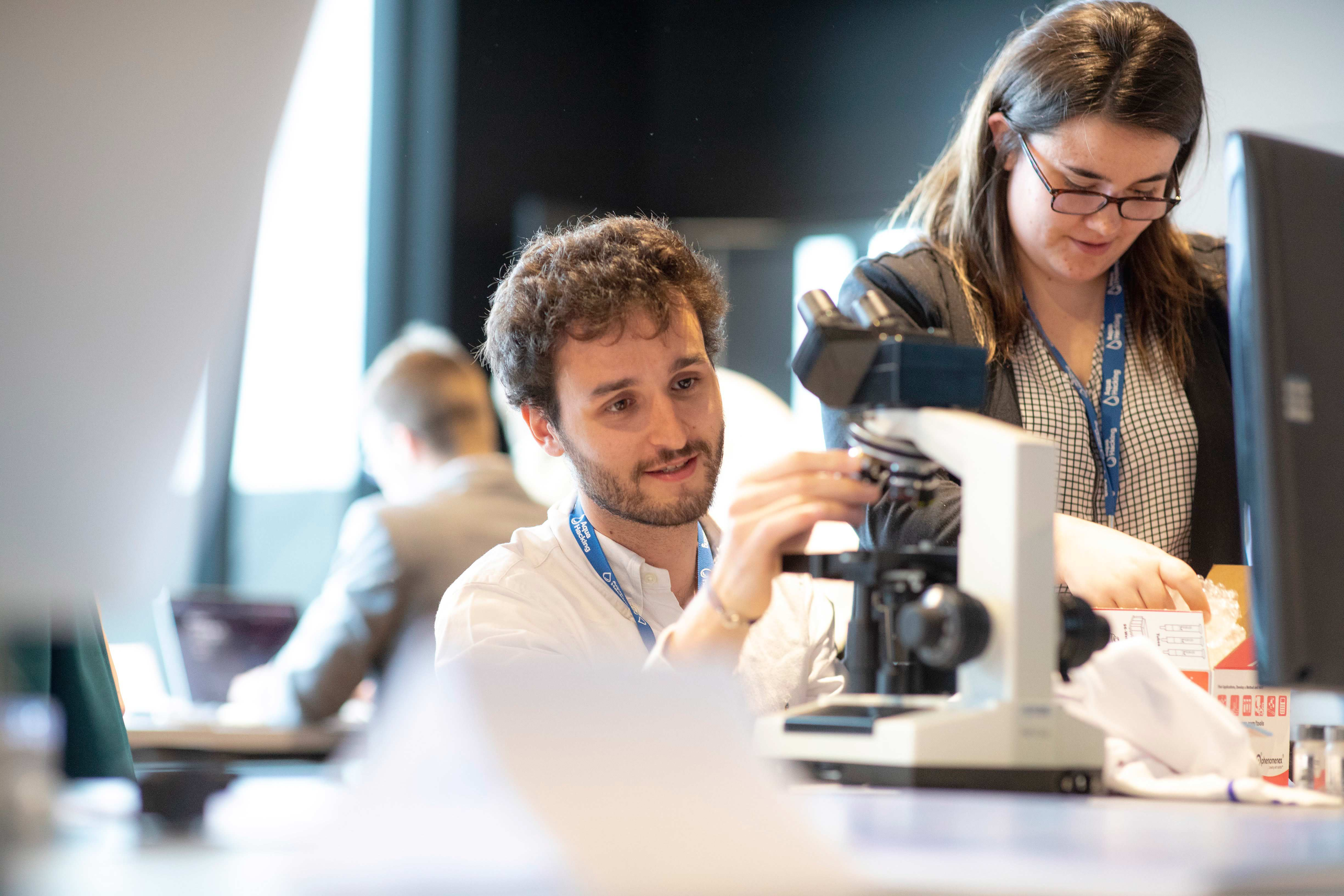 Young man using microscope during AquaHacking event