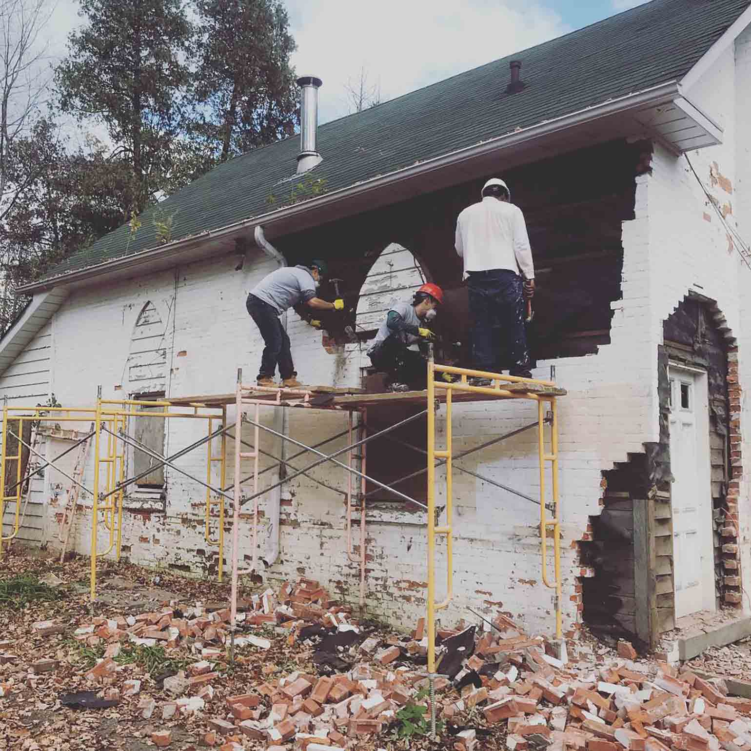 Three workers help demolish a white brick wall for a home renovation to help the homeless.