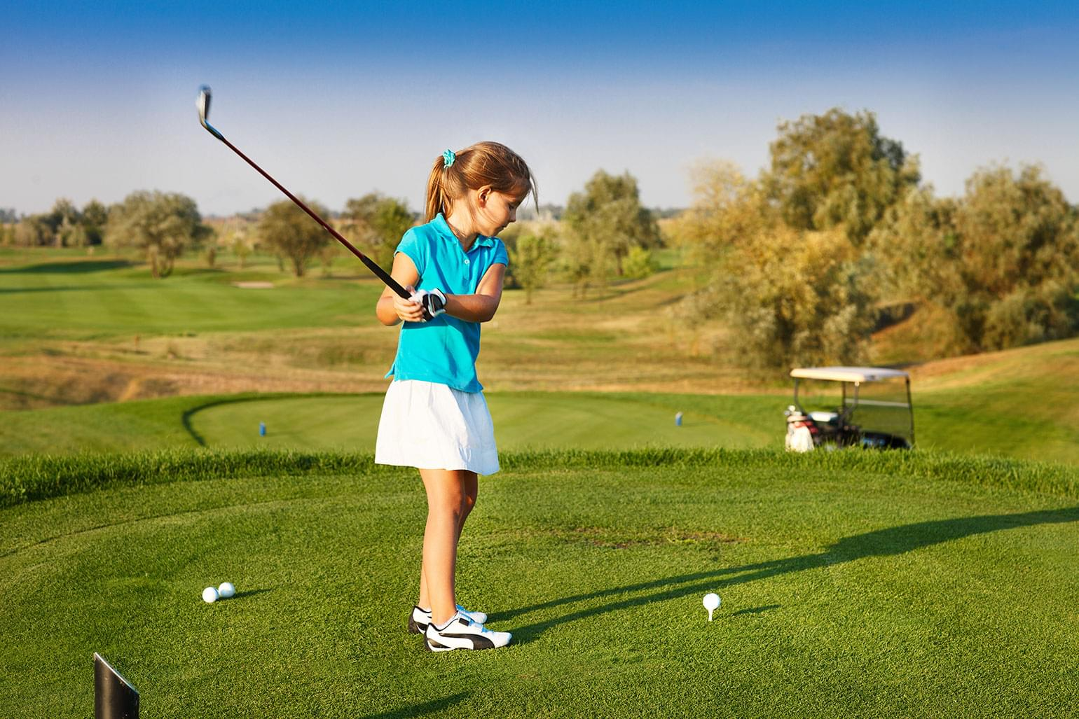 Young girl in skirt and blue golf shirt teeing off.
