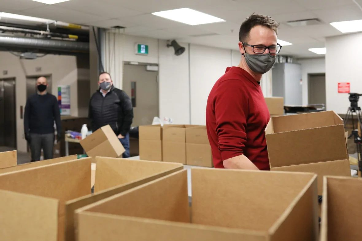 Three masked volunteers sort food donations into boxes inside the Regina Food Bank.