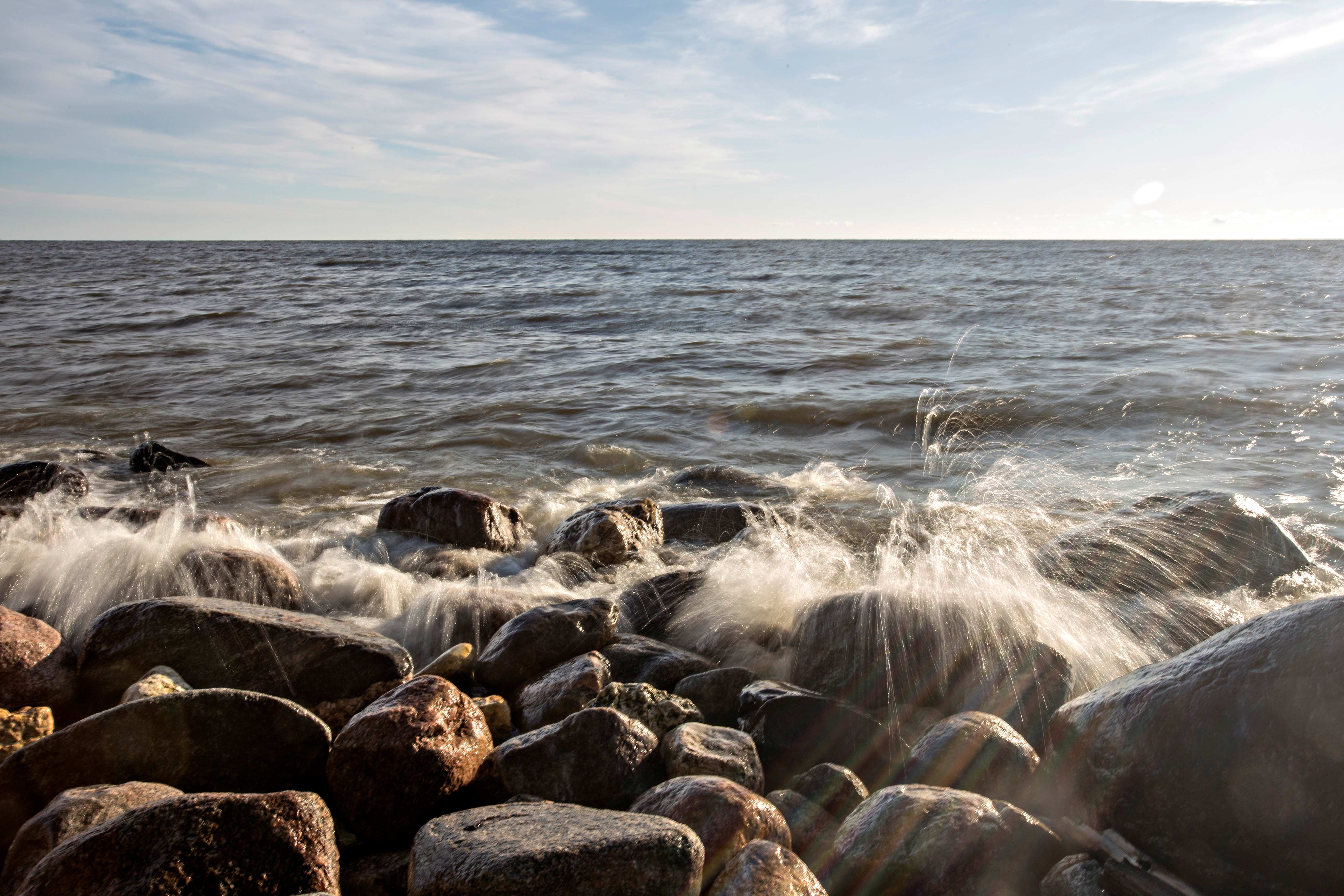 Water splashes over rocks at the shore of Lake Winnipeg.