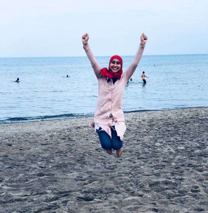 Maria jumping joyfully on a beach.
