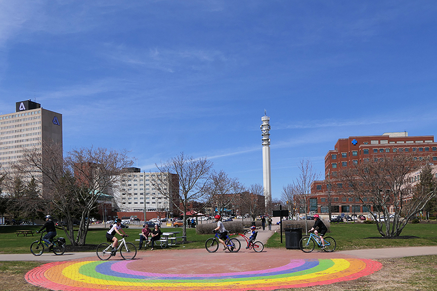 A park plaza on a sunny day in downtown Moncton with young people bicycling, and a rainbow painted on the sidewalk.