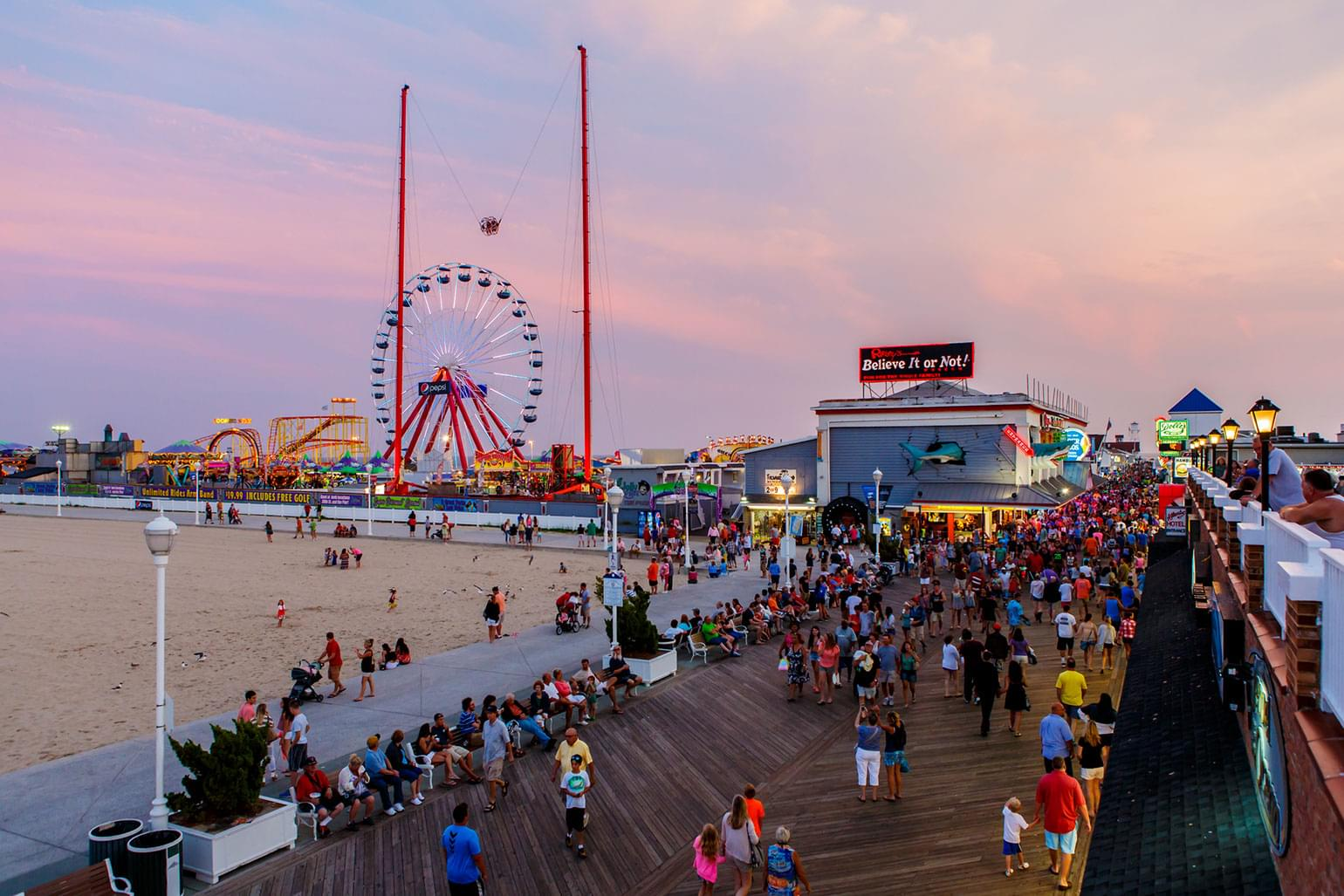 Dusk in Ocean City, Maryland with the boardwalk amusement park lit up.