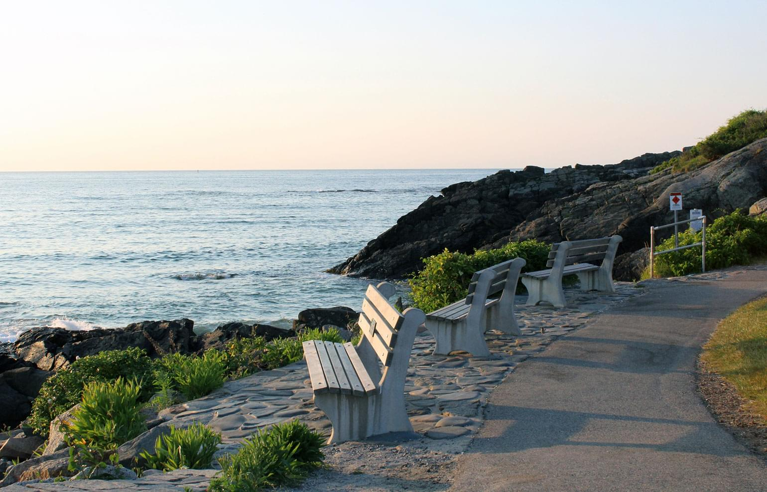 Park benches overlook the shore at sunset in Ogunquit, Maine.