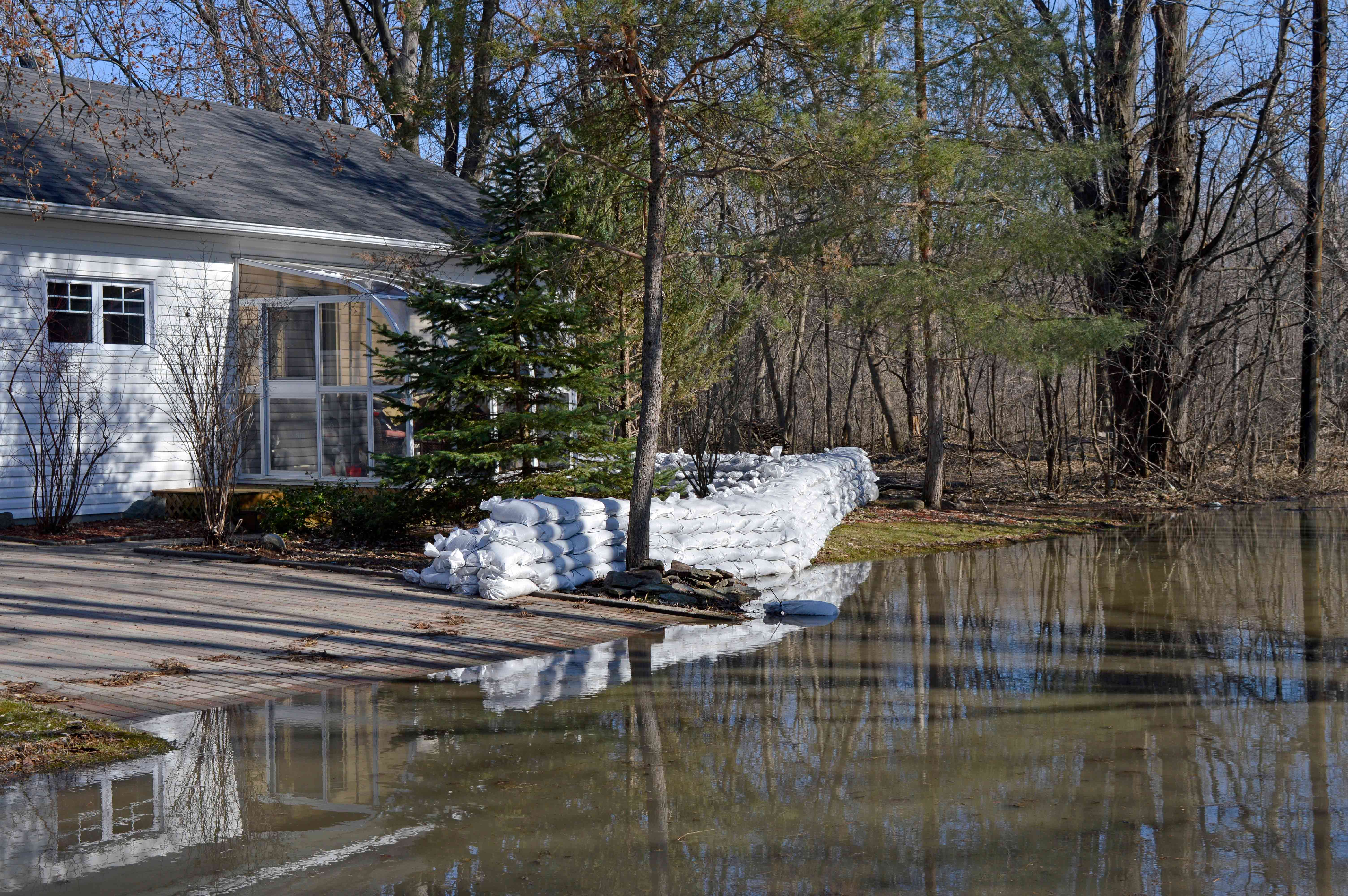 A wall of white sand bags protects a home in a forest in Gatineau, Quebec.
