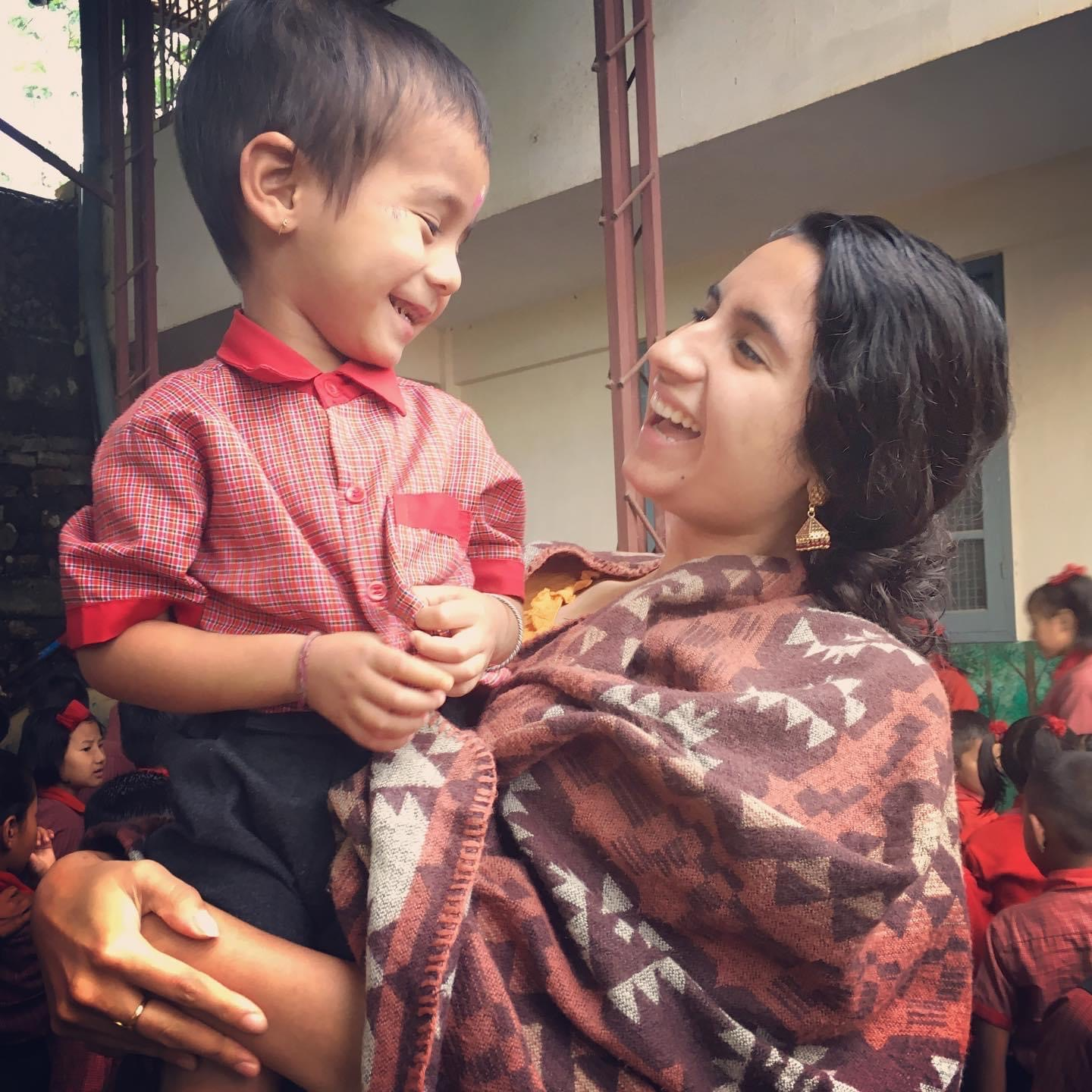 Roshni Thawani holds a smiling young student