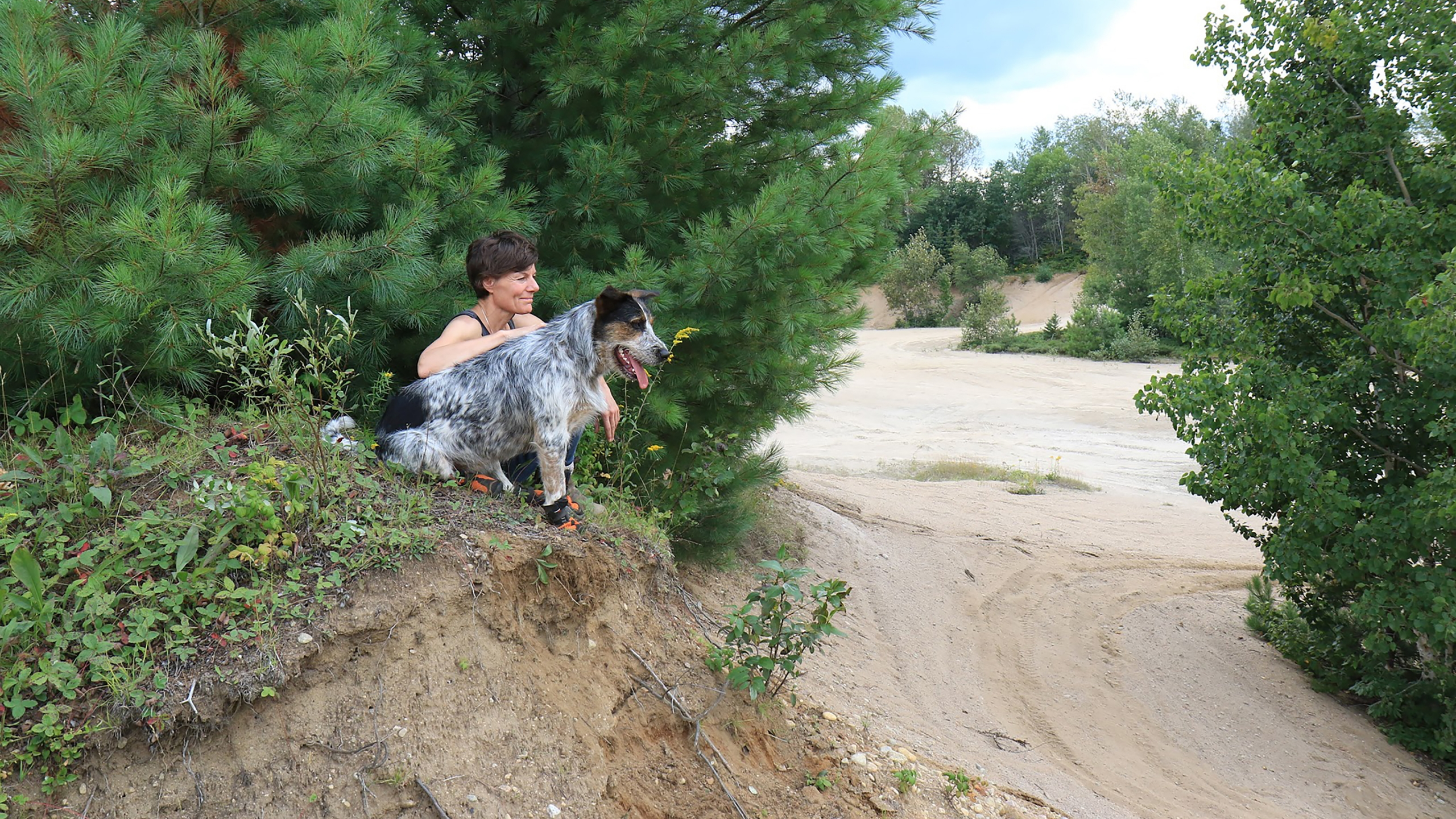 Muttluks founder Marianne Bertrand with a grey spotted dog sitting under a tree