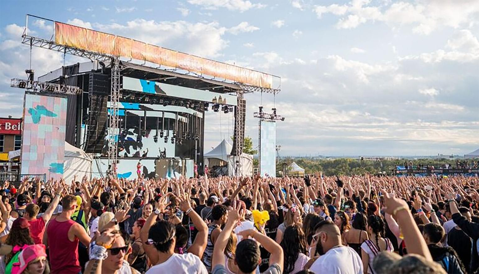 Large crowd at a festival with hands in the air.
