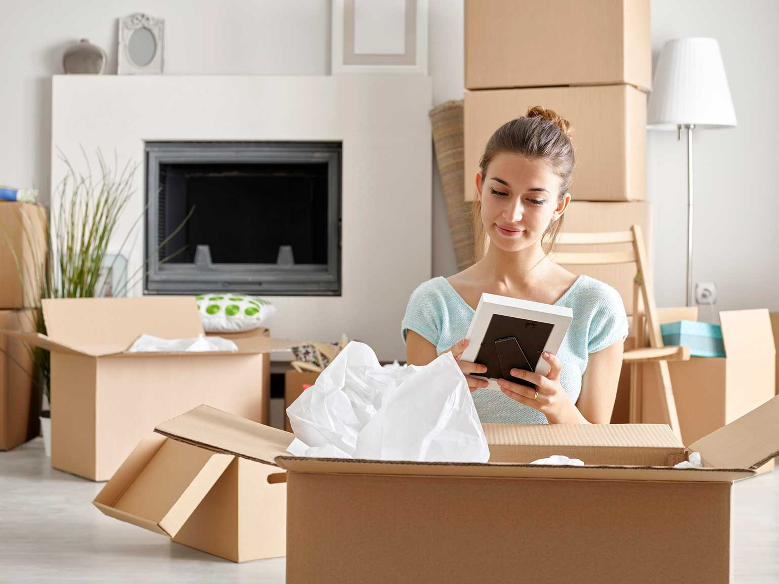 Young woman unpacks a box in her first new home