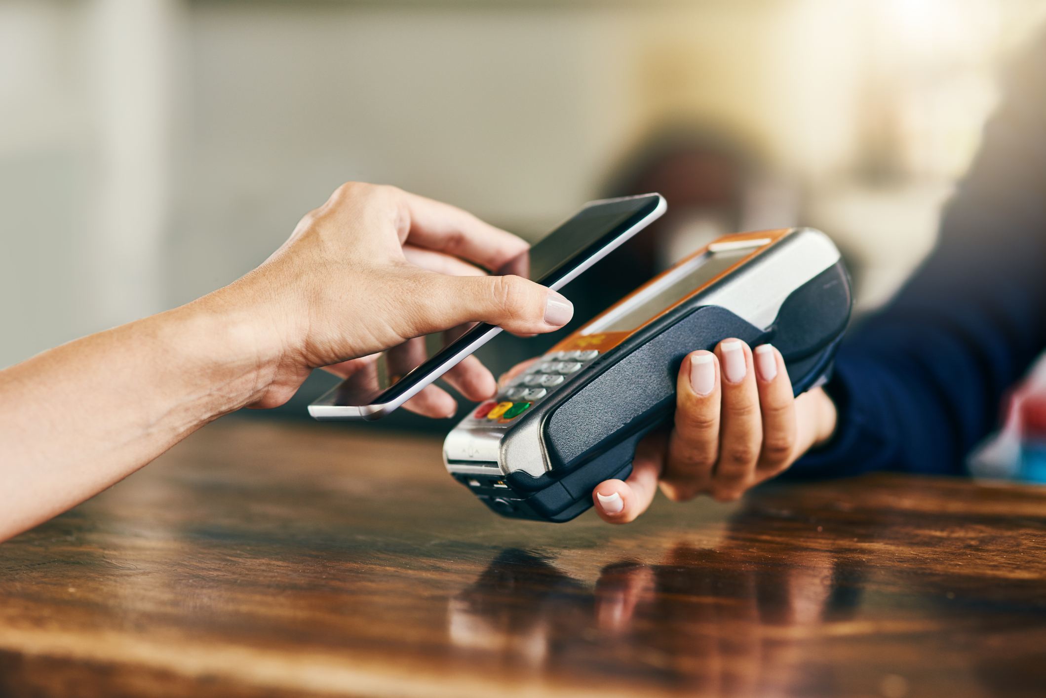 A student uses Mobile Pay on a smartphone to pay at a store with contactless credit payments.