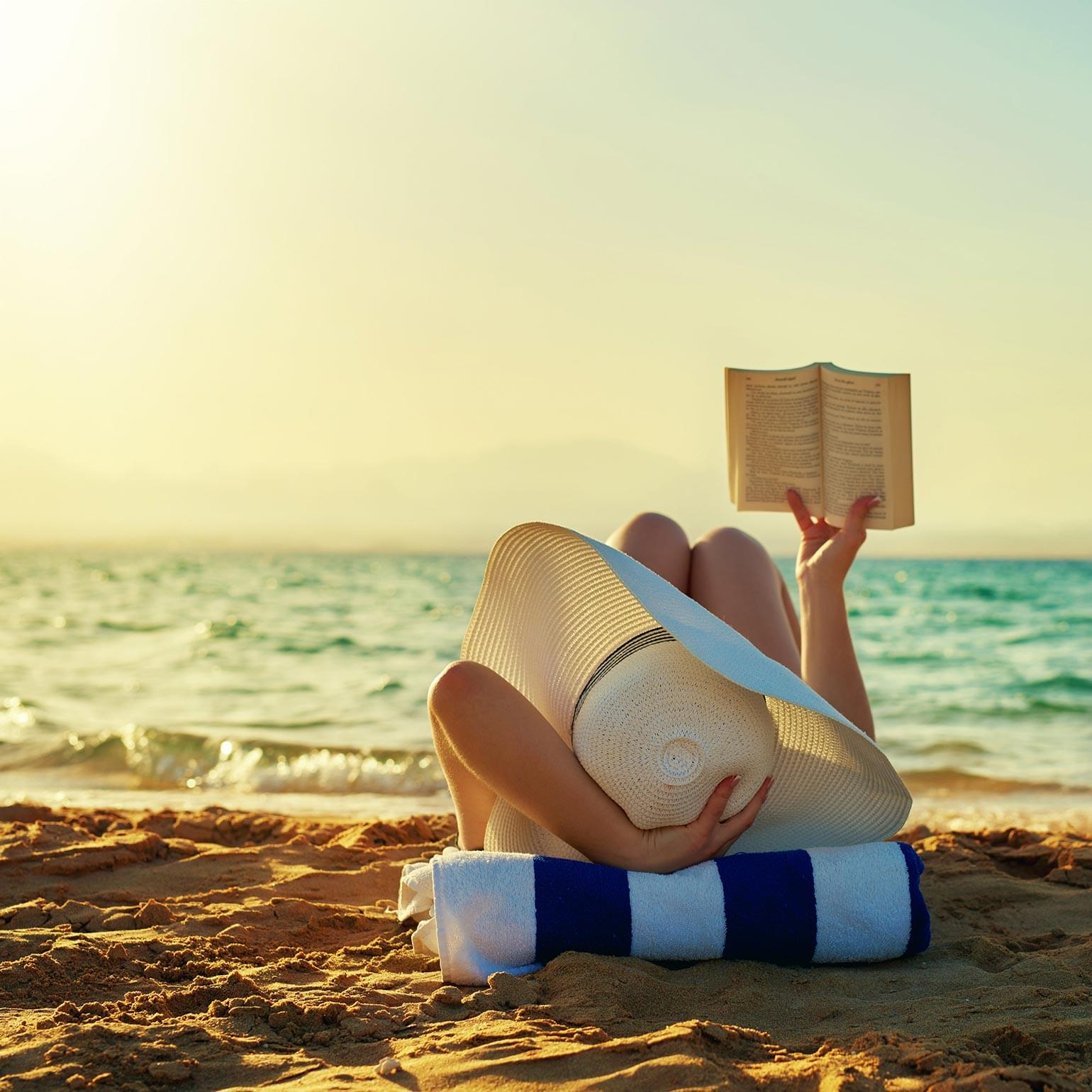 Young woman reads book beachside during sunset.
