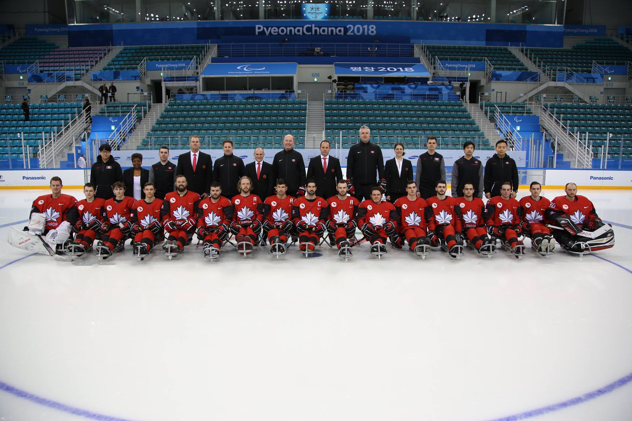 Team Canada posing in an ice rink at the 2018 Paralympic Games.