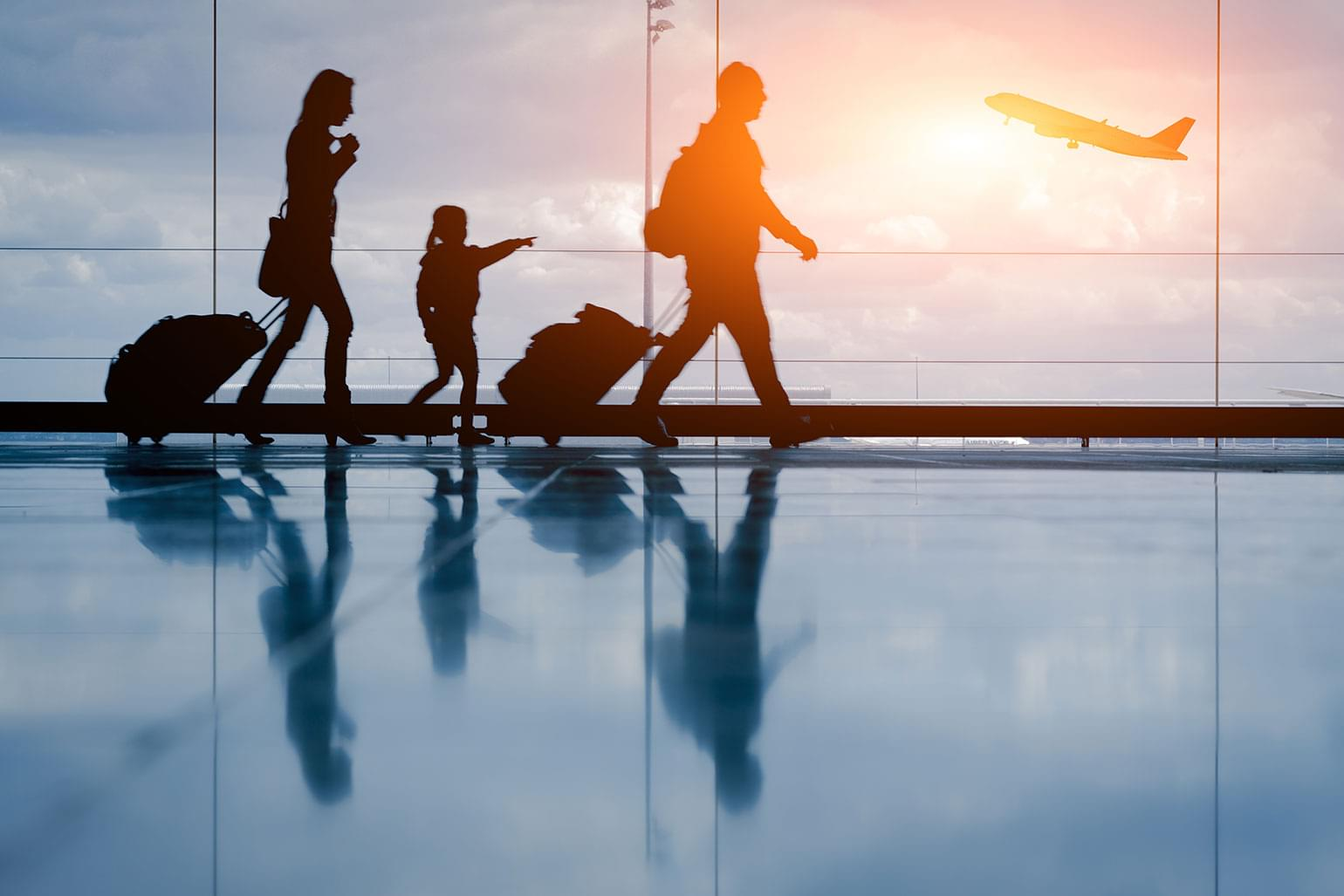 Silhouette of young family with luggage and airplane walking to their gate.