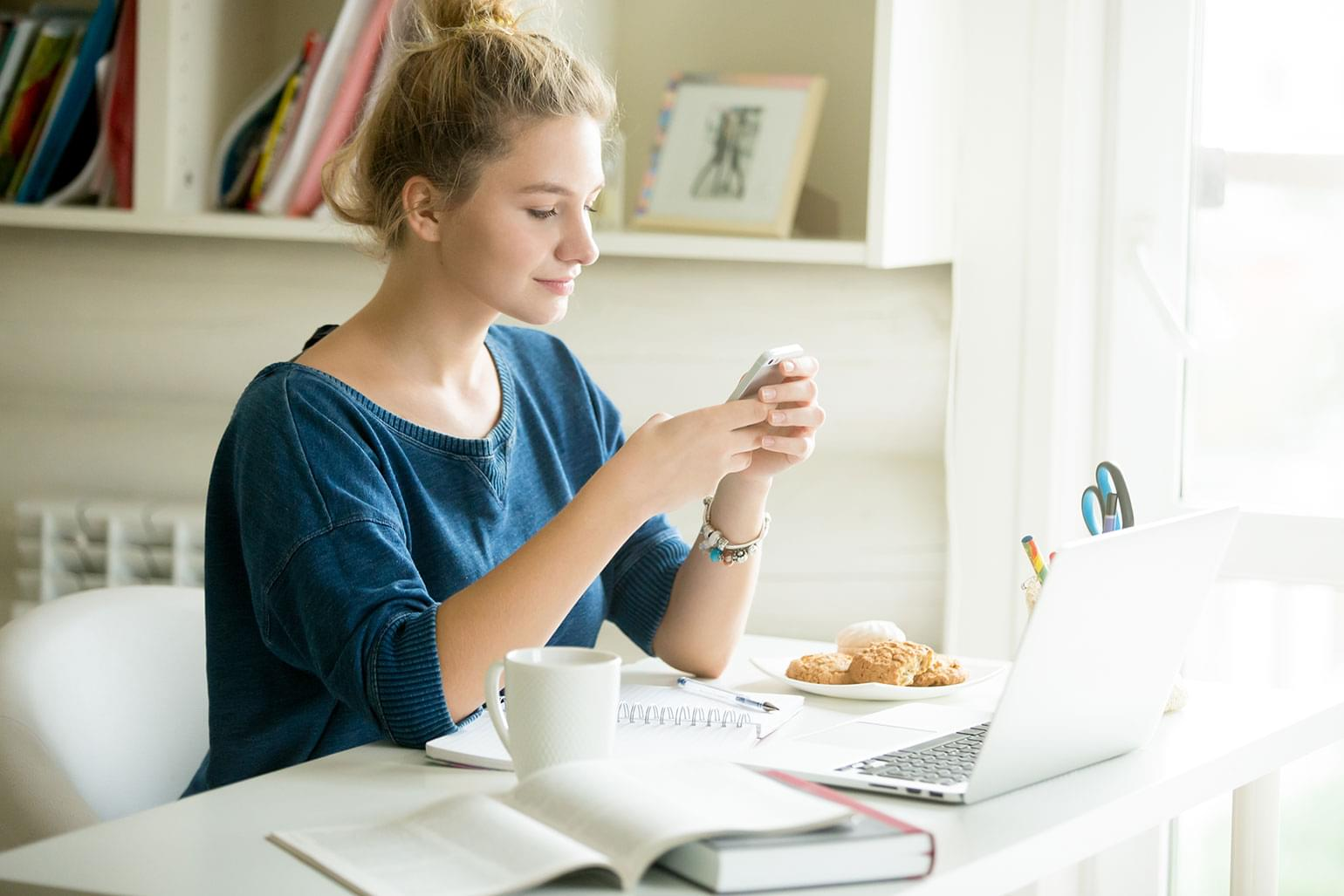 Portrait of young beautiful casual woman holding smartphone, looking at screen, using app or messaging while sitting at modern workplace with laptop, books, coffee and cookies in home office or dorm.